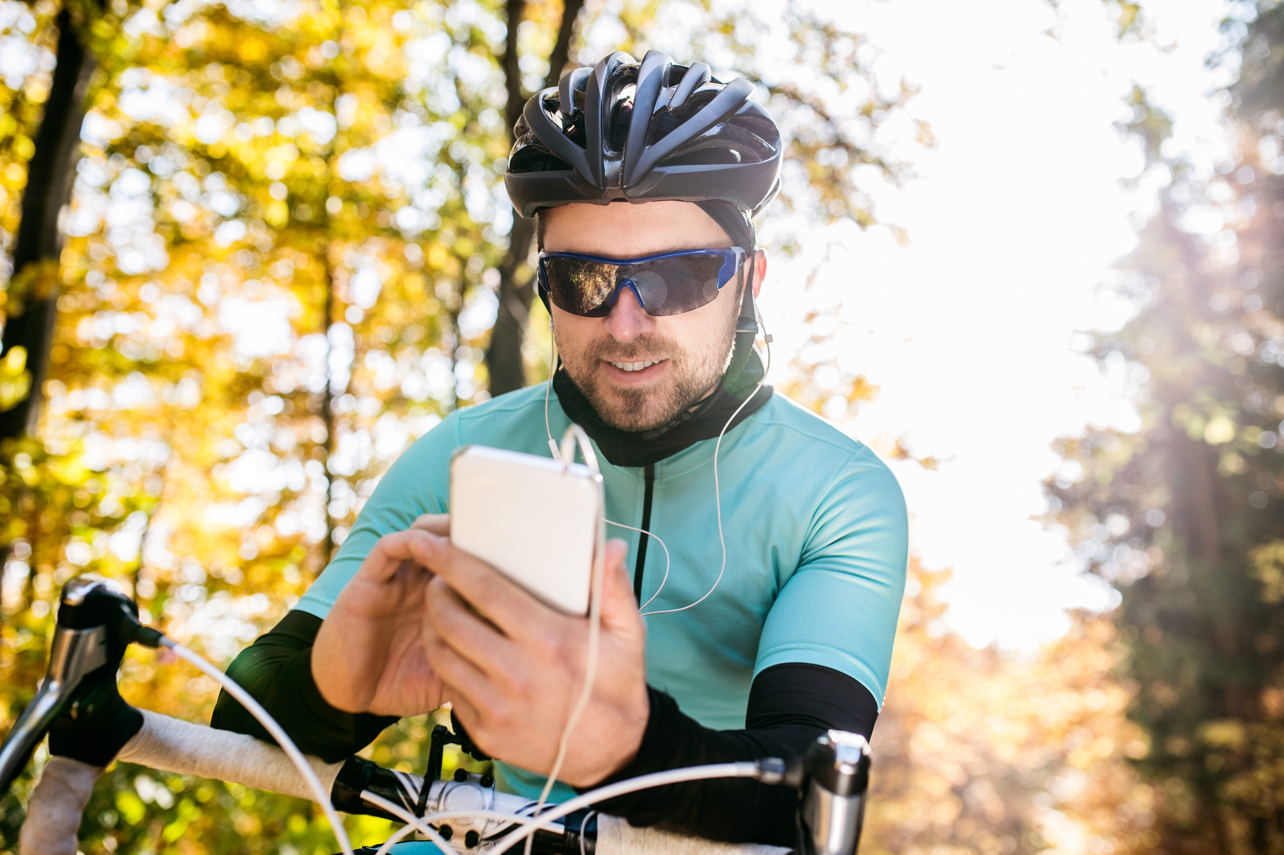 Young sportsman riding bicycle, holding smartphone, sunny autumn
